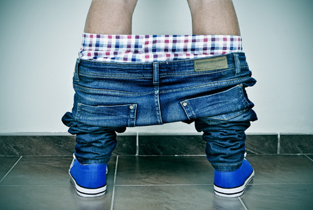 teenager nude: closeup of a young caucasian man with his denim pants and his underwear down, seen from behind Stock Photo