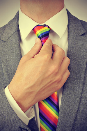 sexual orientation: closeup of a young caucasian businessman tightening the knot of his rainbow necktie, with a slight vignette added