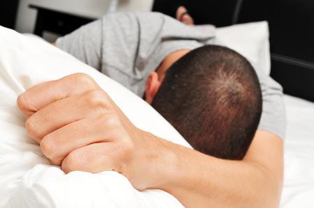 Primo piano di un giovane uomo caucasico a faccia in giù sul letto stringendo forte il suo cuscino Archivio Fotografico - 41047880
