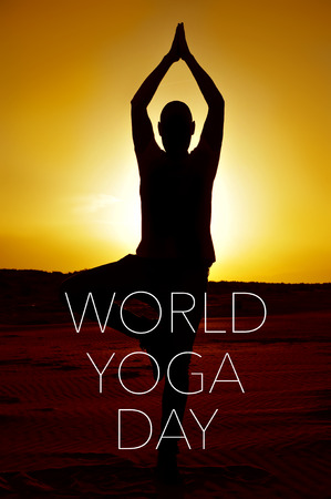 anjali: a young yogi man practicing the tree pose outdoors in backlight at sunset and the text world yoga day