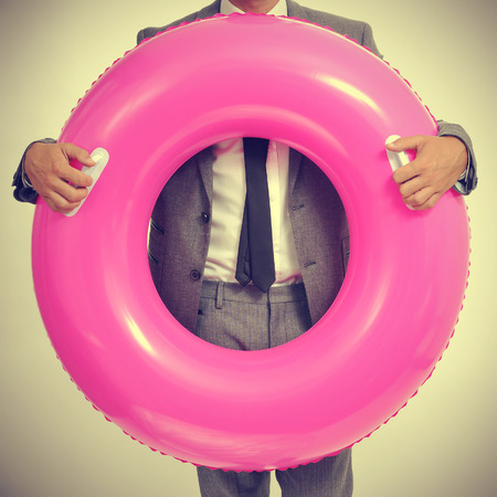 headman: a young caucasian businessman wearing a grey suit with a pink swim ring, with a retro effect
