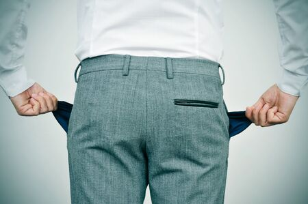 impoverish: broke businessman wearing white shirt and grey trousers shows his empty pockets, seen from behind