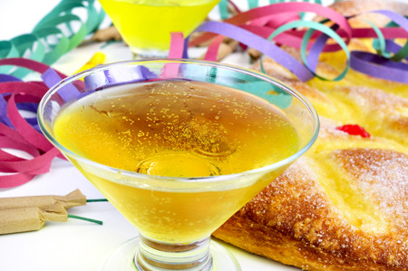 sant: closeup of two glasses with champagne, some firecrackers and streamers, and a coca de Sant Joan, a typical sweet flat cake from Catalonia, Spain eaten on Saint Johns Eve