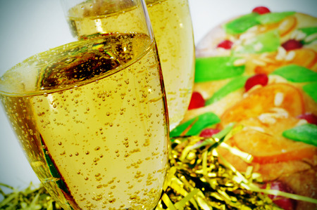 sant: closeup of two glasses with champagne and a coca de Sant Joan, a typical sweet flat cake from Catalonia, Spain eaten on Saint Johns Eve