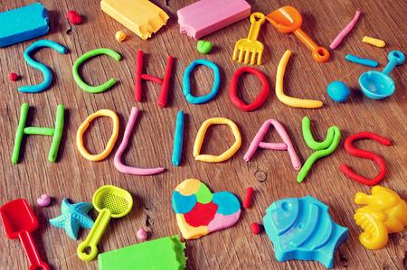 다양한 색상과 같은 장난감 삽과 모래 금형 등 일부 해변 장난감의 클레이 모델링에서 만든 텍스트 방학, 소박한 나무 표면에