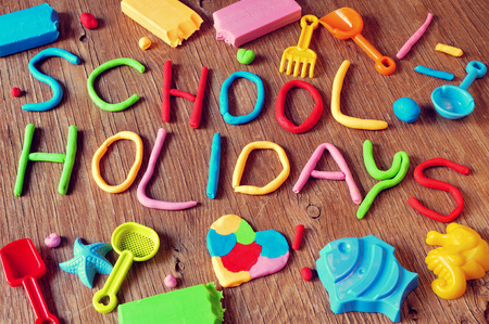 kids playing beach: the text school holidays made from modelling clay of different colors and some beach toys such as toy shovels and sand moulds, on a rustic wooden surface Stock Photo