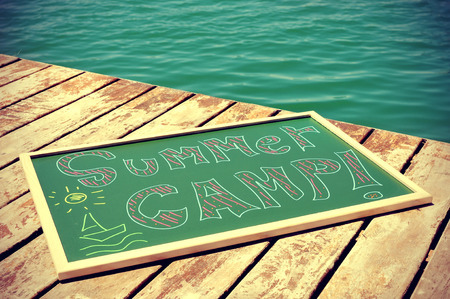 vignetted: the text summer camp written with chalk of different colors in a chalkboard, on a wooden pier on the sea, slight vignette added