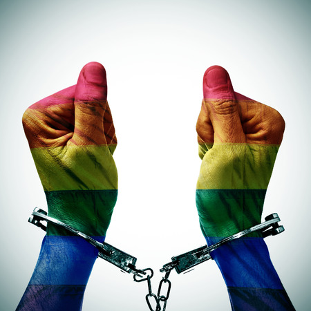 hombres gays: primer plano de las manos hancduffed de un hombre joven con dibujos como la bandera del orgullo gay, para denunciar la criminalizaci�n de la homosexualidad en algunos pa�ses Foto de archivo