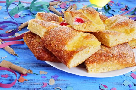 juan: some firecrackers and a plate with pieces of coca de Sant Joan, a typical sweet flat cake from Catalonia, Spain, eaten on Saint Johns Eve, on a rustic blue table full of confetti and streamers
