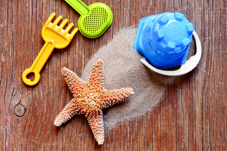 beach toys: high-angle shot of a rustic wooden surface with a starfish on a pile, and some beach toys such as a shovel, a rake and a pail Stock Photo