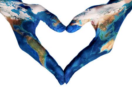 les mains d'une jeune femme formant un coeur à motifs avec une carte du monde (fournie par la NASA), sur un fond blanc Banque d'images