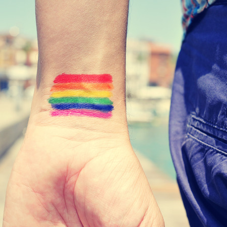 transgender: closeup of a young caucasian man seen from behind with a rainbow flag painted in his wrist