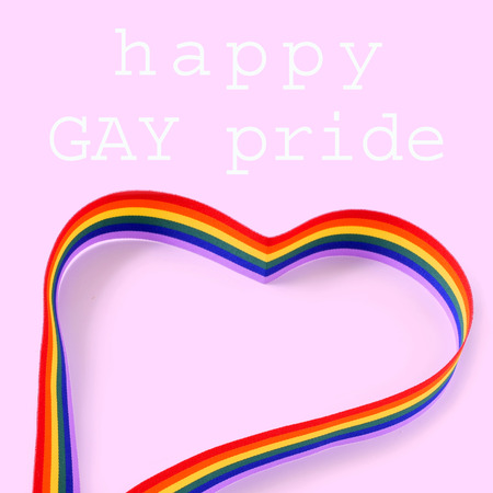 lesbianism: a rainbow ribbon forming a heart and the text happy gay pride day written on a pink background
