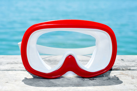 diving mask: closeup of a red and white diving mask on an old wooden pier above the sea