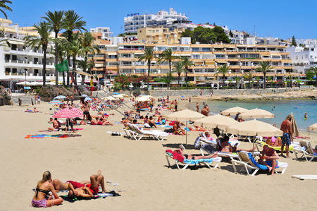 beaches of spain: Ibiza Spain  June 19 2015: Sunbathers in the popular Ses Figueretes Beach in Ibiza Town Spain. Ibiza is a wellknown summer tourist destination in Europe