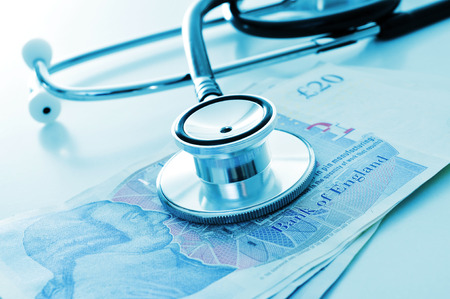 health industry: a stethoscope on a pile of pound sterling bills, depicting the concept of the health care industry in the United Kingdom Stock Photo