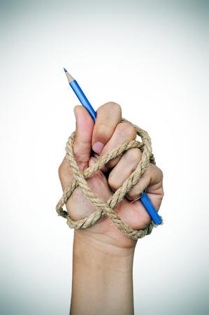 derechos humanos: la mano de un hombre atado con una cuerda, sosteniendo un lápiz, que representa la idea de la represión de la libertad de prensa o la libertad de expresión Foto de archivo