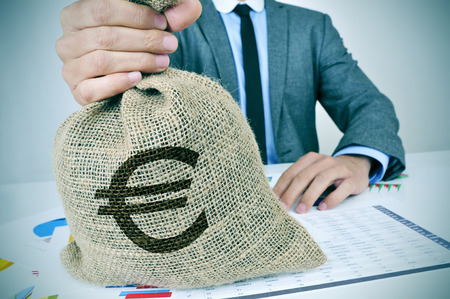 a young caucasian man wearing a gray suit seated at an office desk full of charts and financial balances holds a burlap money bag with the euro currency sign in his hand Archivio Fotografico