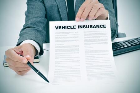 seguro: un hombre caucásico joven que llevaba un traje gris en su oficina muestra una póliza de seguro de vehículos y puntos con un lápiz donde el asegurado debe firmar