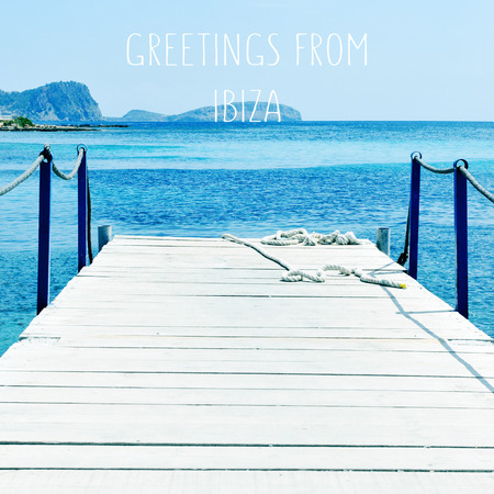 baleares: an aged wooden boardwalk over the Mediterranean sea in Ibiza Island, Spain, and the text greetings from Ibiza, with a retro effect