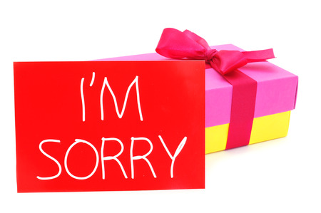 regretful: a gift box of different colors tied with a purple ribbon and a red card with the text I am sorry written in it, on a white background Stock Photo