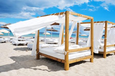 Detail einige Betten und Sonnenliegen in einem Beach-Club in einem weißen Sandstrand in Ibiza, Spanien