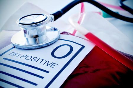 O RH プラス テキスト付きのラベルと聴診器と血液バッグのクローズ アップ