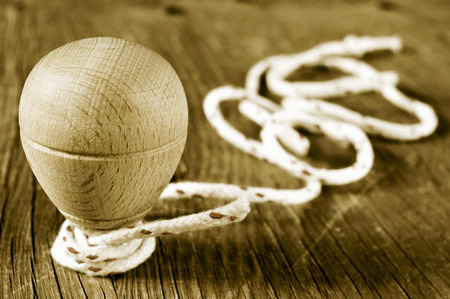 string top: a traditional wooden spinning top with a string coiled in its axis on a rustic wooden surface, in sepia toning