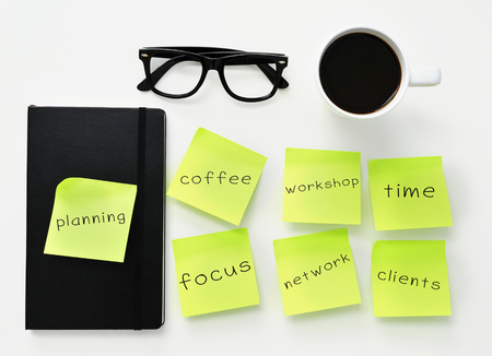 freelance: high-angle shot of a white office desk with a cup of coffee, a black notebook, a pair of black plastic-rimmed eyeglasses and some yellow sticky notes with different work concepts Stock Photo