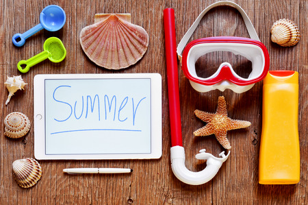 souvenir: high-angle shot of a rustic wooden table full of summer stuff, such as a starfish, some seashells, a diving mask and a snorkel, a bottle of sunblock and a tablet with the word summer written in it
