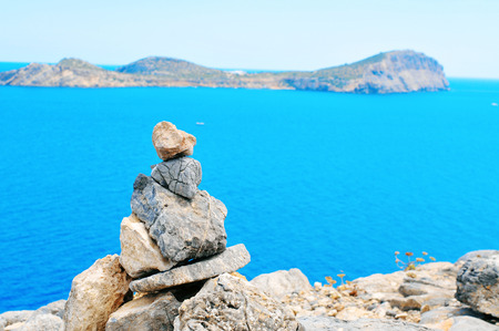 sea mark: closeup of a stack of balanced stones in Ibiza Island, in Spain, with the Mediterranean sea and the Tagomago Island in the background