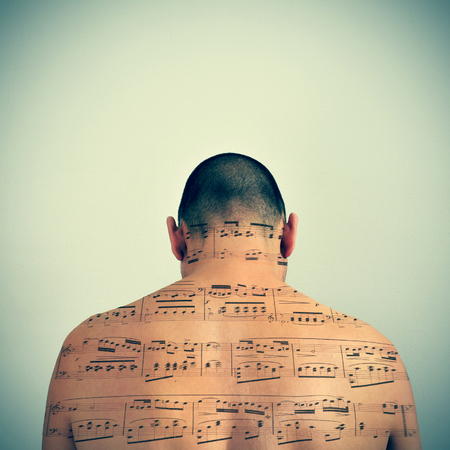 musical score: a young caucasian man with a musical score patterned in his back, with a retro effect Stock Photo