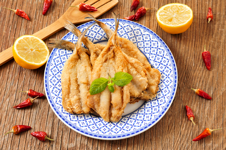 engraulis: closeup of a plate with spanish boquerones fritos, battered and fried anchovies typical in Spain, on a rustic wooden table