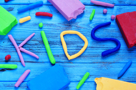 modelling clay: modelling clay of different colors forming the word kids on a blue wooden surface