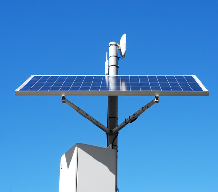 panel: closeup of a solar panel installed in the top of a pole, over the blue sky Stock Photo