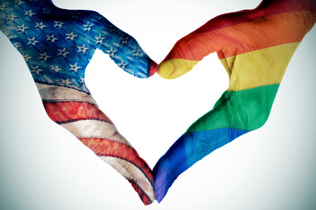 same sex: woman hands forming a heart patterned with the rainbow flag and the flag of the United States, depicting the legalization of the same-sex marriage in this country Stock Photo
