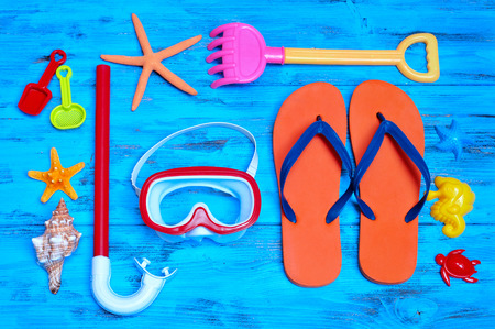 beach toys: high-angle shot of a rustic blue wooden table full of summer stuff, such as some starfishes, a conch, a diving mask and a snorkel, a pair of flip-flops and some beach toys Stock Photo
