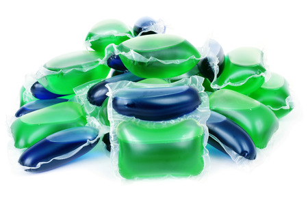 sachets: closeup of a pile of liquid laundry detergent sachets on a white background
