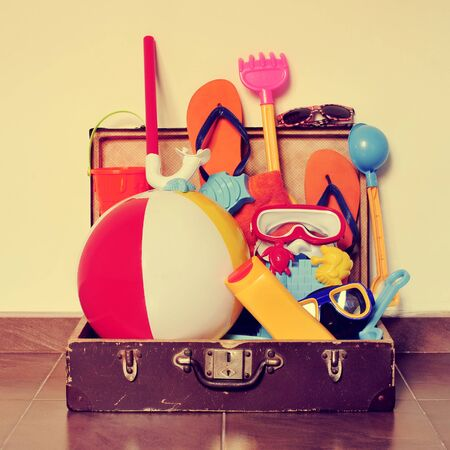 old items: an old cardboard suitcase full of beach items, such as diving masks, pails and shovels, a beach ball, sunblock or flip-flops, placed on the floor, with a retro effect Stock Photo