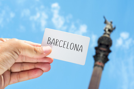 wanderlust: closeup of the hand of a young man showing a signboard with the text Barcelona, with the famous Columbus Monument in the background in Barcelona, Spain