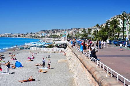 nice: Nice, France - May 16, 2015: People sunbathing on the beach in Nice, France. The long and famous seafront of Nice bordering the Mediterranean Sea is known as the Promenade des Anglais