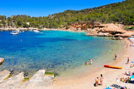 antonio: San Antonio, Spain - June 18, 2015: Sunbathers at Cala Salada beach in San Antonio, Ibiza Island, Spain. Ibiza is a well-known summer tourist destination in Europe Editorial