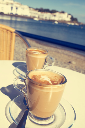 cortado: closeup of two glasses with caffe macchiato on a table in the terrace of a cafe in the seafront of Cadaques, in the Costa Brava, Spain