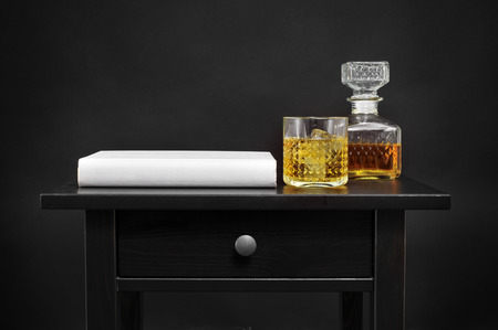 prose: a book, and a bottle and a lowball glass with liquor on a black table, over a black background Stock Photo