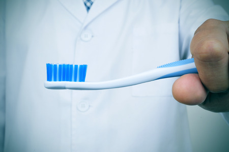 periodontal: a dentist showing a toothbrush depicting the importance of tooth brushing for a good oral hygiene