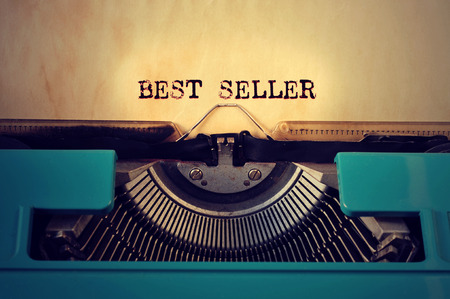 closeup of a blue retro typewritter and the text best seller written with it in a yellowish foil Stok Fotoğraf