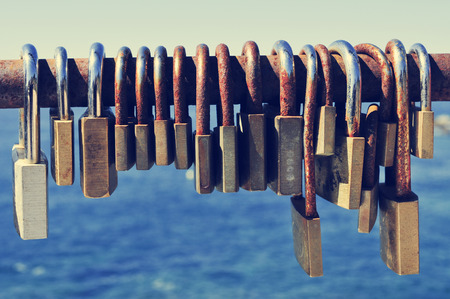 wanderlust: closeup of a lot of rusty padlocks locked in the crossbar of a rusty railing near the sea