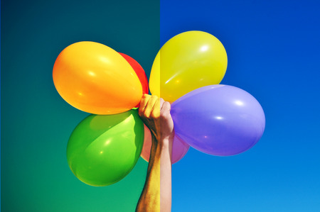 saturate: man holding a bunch of balloons of different colors before (right) and after (left) applying a filter during the image editing process