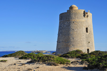 neighboring: a view of the medieval tower Torre de Ses Portes in Ibiza Island, Spain, and the neighboring Formentera Island in the background