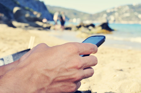 millennial: closeup of a young caucasian man using a smartphone on the beach Stock Photo